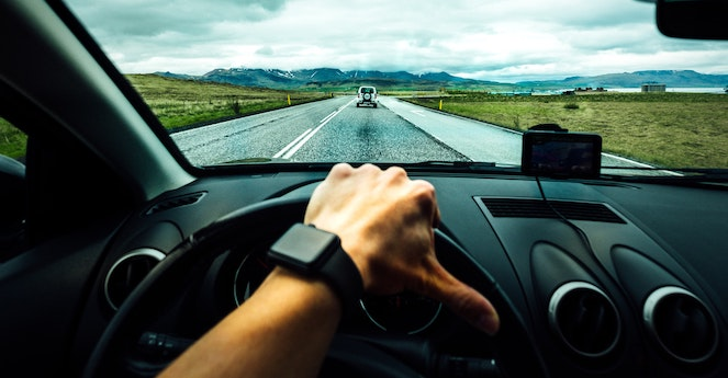 View of a hand on a car's steering wheel, driving down a country road