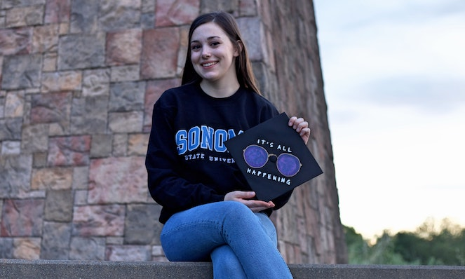 Young female student smiling as she poses with her personalized graduation cap