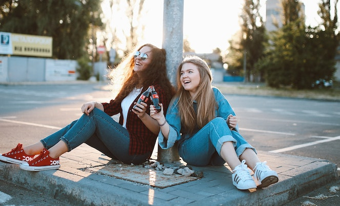Two young girls sitting on the ground at an empty parking lot laughing together