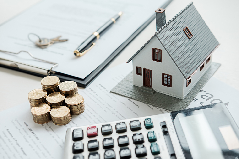 small model home beside a calculator and stack of coins