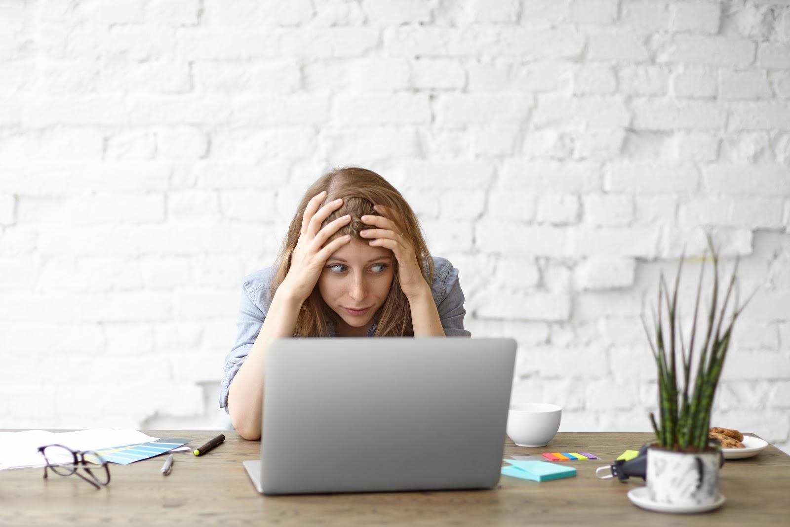 Woman crouching behind laptop