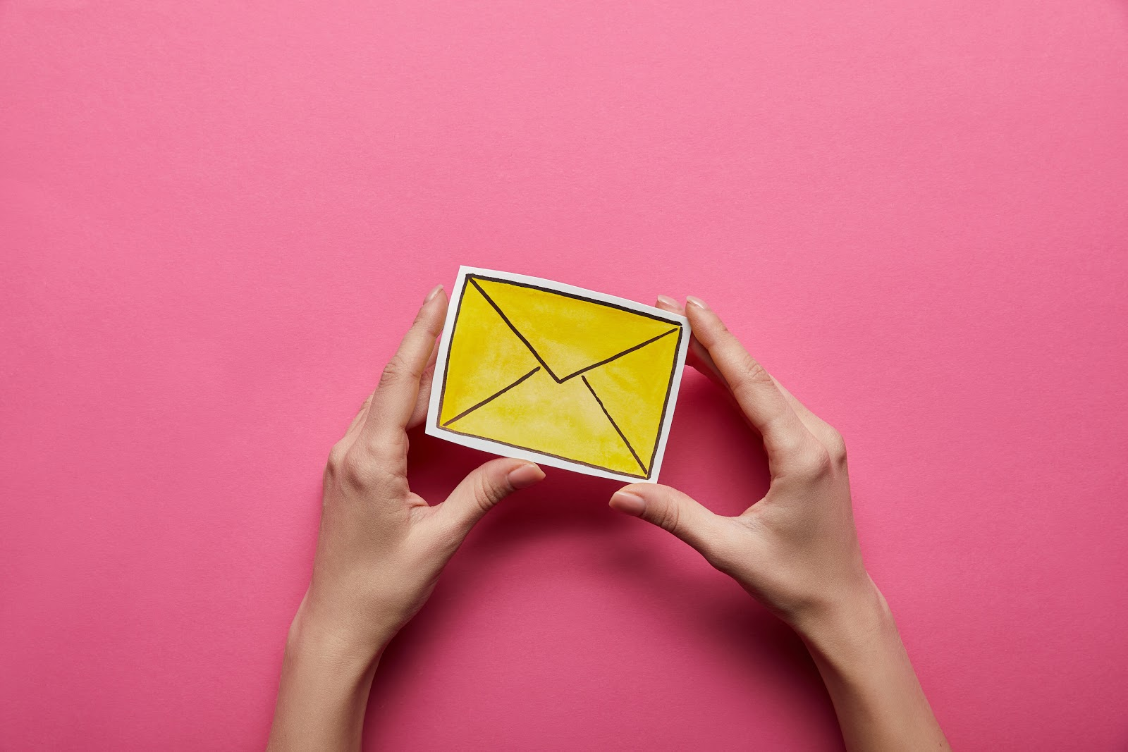 Hands holding illustrated envelope in front of pink background