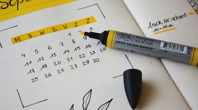 Yellow highlighter sitting on top of a calendar