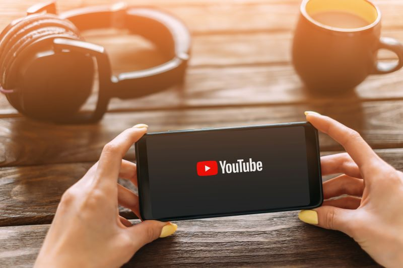 Hands holding a smartphone with YouTube app