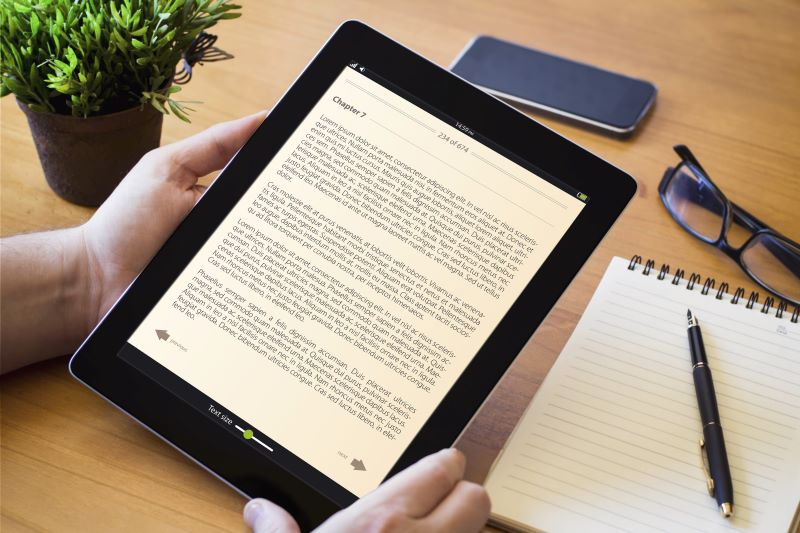 Lead generation strategies: Hands holding an e-book on a desk