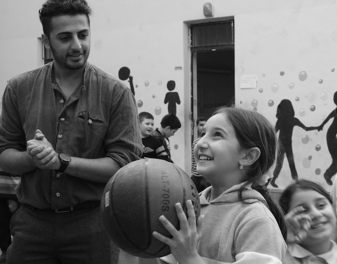 Young girl smiling as she's about to shoot a basketball at recess