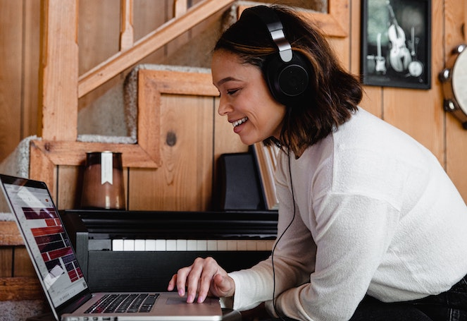 Young woman wearing headphones smiles as she works on her laptop