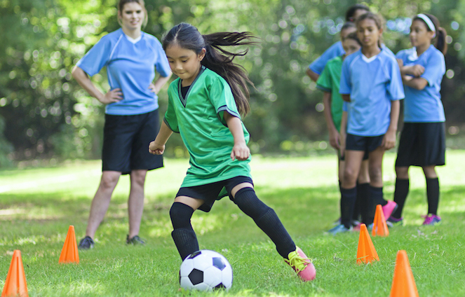 Young girl dribbling a soccer ball during a practice drill