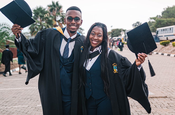 Young man and woman happily pose with cap and gown after graduating